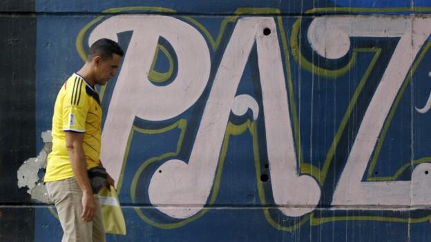 Ein Mann geht im kolumbischen Cali an einer Mauer vorbei, darauf steht das spanische Wort paz für Frieden, er trägt das gelbe Shirt der kolumbischen Fussballnationalmannschaft.