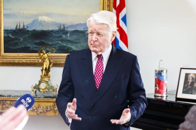 Islands Präsident Olafur Ragnar Grimsson in der Hauptstadt Reykjavik vor Journalisten, hinter ihm die isländische Flagge an der Wand. Grimsson hat graue Haare und trägt einen Anzug.