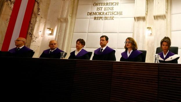 Zu sehen sind die Richter am österreichischen Verfassungsgericht, die über angebliche Fehler rund um die Bundespräsidentenwahl vom Mai verhandeln.