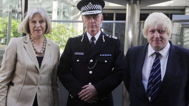 Eine Frau und ein Mann, links und rechts eines Polizisten.