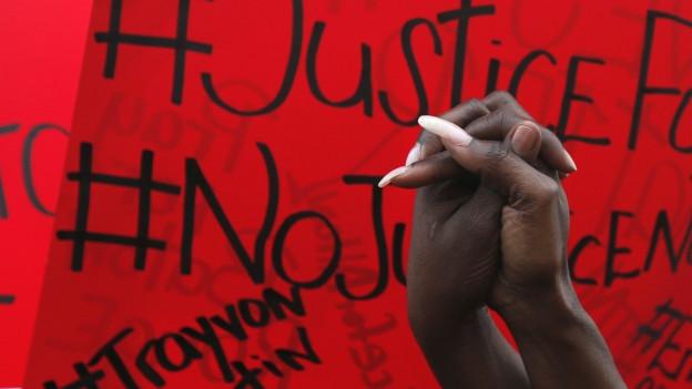 Eine Afroamerikanerin und ein Afroamerikaner halten sich an der Hand; im Hintergrund ein Protestplakat.
