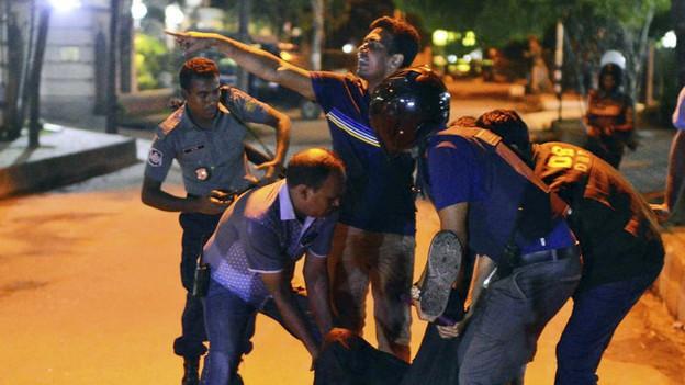 Verletzte werden während der Erstürmung des belagerten Restaurants geborgen