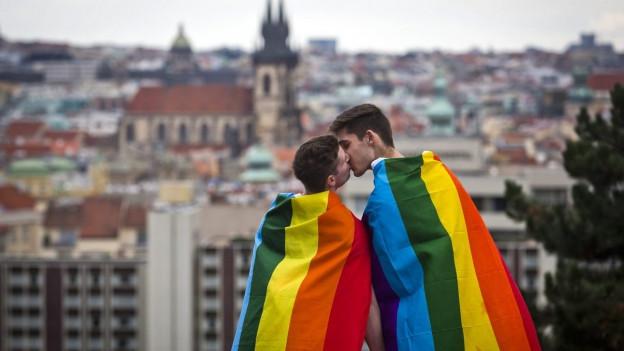 Zwei Männer, gehüllt in die Regenbogenfahne, küssen sich vor der Prager Kulisse.