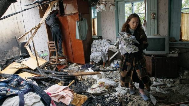 Ein Paar in seinem zerstörten Haus in Donezk, sie im Vordergrund, ihn sieht man von hinten im Hintergrund, alles ist voller Trümmer (9. Juni 2016).