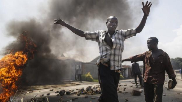 Zwei Demonstranten vor einem brennenden Auto in Burundis Hauptstadt Bujumbura, einer wirft die Hände in die Luft, Rauch ist am Himmel (3. Juni 2015).