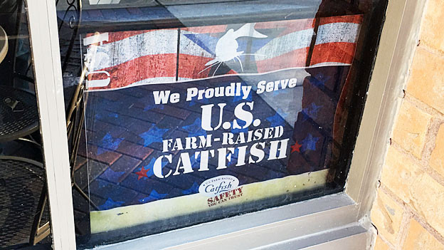 «We proudly serve U.S. farm-raised Catfish» steht am Fenster eines Fischrestaurants.