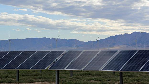 In einer Ebene stehen Sonnenkollektoren und Windräder, dahinter eine Bergkette.