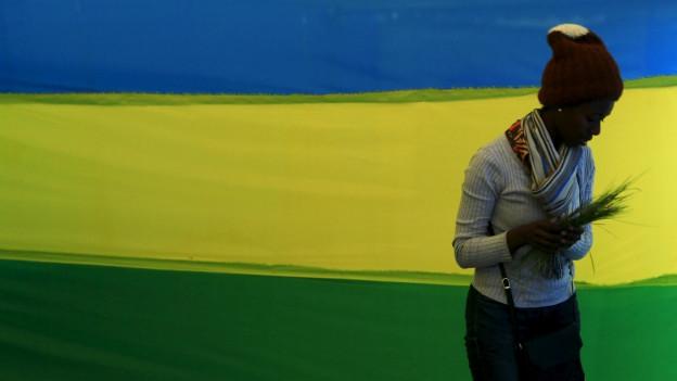Eine Ruanderin steht vor einer Wand, die in den Nationalfarben blau, gelb, grün gestrichen ist.