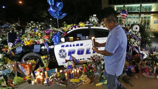 Ein Mann bringt in Dallas eine Kerze zu einem Polizeiauto, das mit Blumen bedeckt ist.