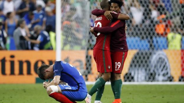 Zwei portugiesische Spieler auf dem Spielfeld in St. Denis umarmen und freuen sich, ein französischer Spieler kauert traurig davor.