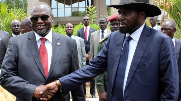 Zu sehen sind die beiden Widersacher: Präsident Salva Kiir (rechts) und Vizepräsident Riek Machar (links). Sie schütteln sich die Hände.