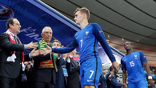 François Hollande schüttelt Mitgliedern der französischen Fussballnati die Hand.