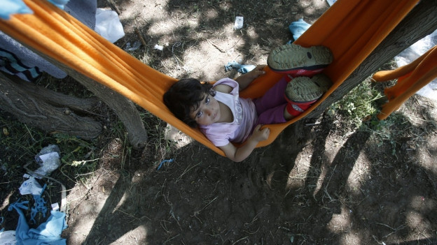 Ein geflüchtetes Mädchen mit traurigem Blick liegt in einer Hängematte.