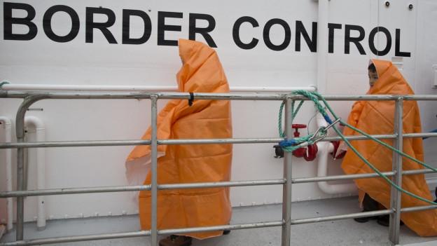 Zwei Kinder, in orange Decken gehüllt, auf einem Schiff der Grenzwache.