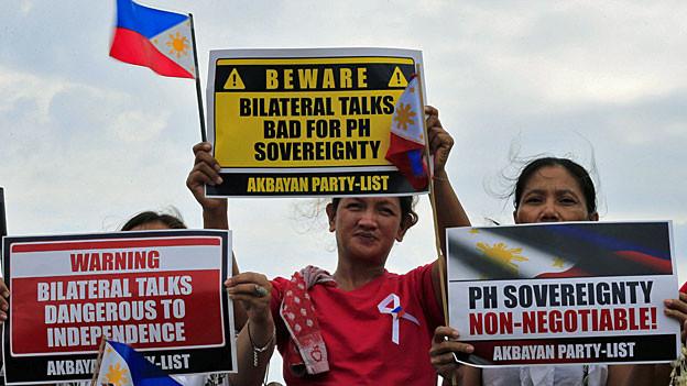 Proteste philippinischer Aktivistinnen in Manila. Auf den Plakaten steht etwa: «Die Souveränität der Philippinen ist nicht verhandelbar».