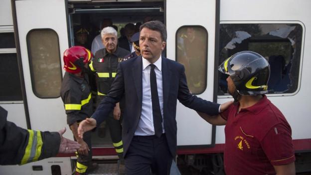 Matteo Renzi steigt aus einem Zug und begrüsst die Helfer vor Ort.