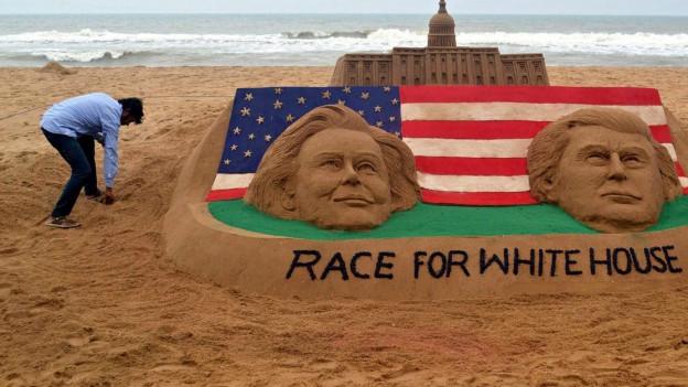 Eine Sandskulptur am Meer mit den Gesichtern von Clinton und TRump.