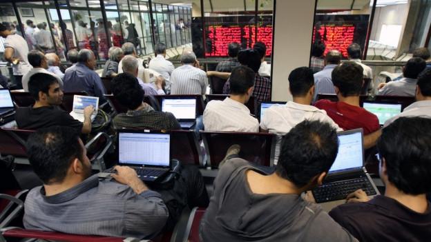 Händler sitzen abwartend vor ihren Computern.