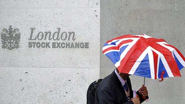 Ein Mann mit Regenschirm in den britischen Farben geht an der Londoner Börse vorbei.