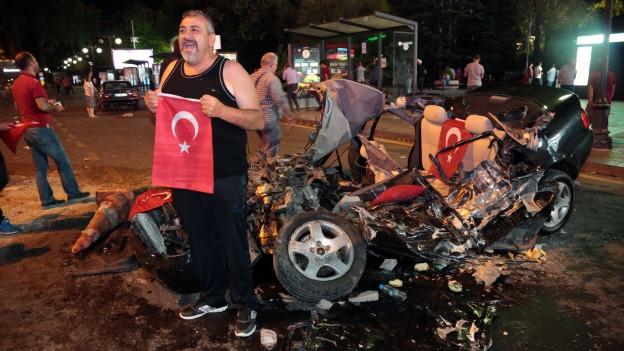 Mann hält türkische Flagge neben Autowrack