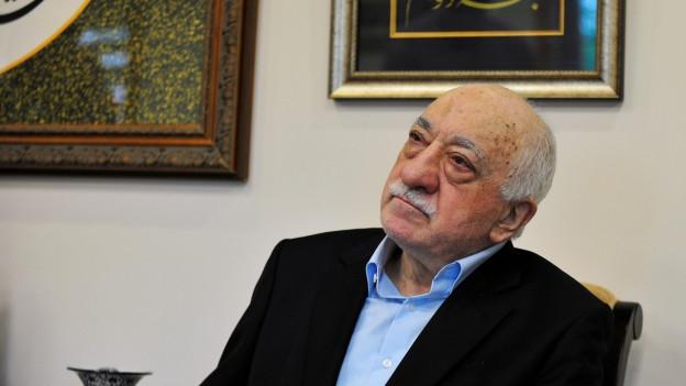 Portrait von Fethullah Gülen vor einem bild mit einem arabischen Schriftzeichen.