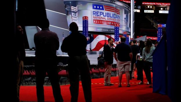 Plakate der Republikanischen Partei im Convention Center in Cleveland, im Vordergrund die schwarzen Umrisse von mehreren Personen.