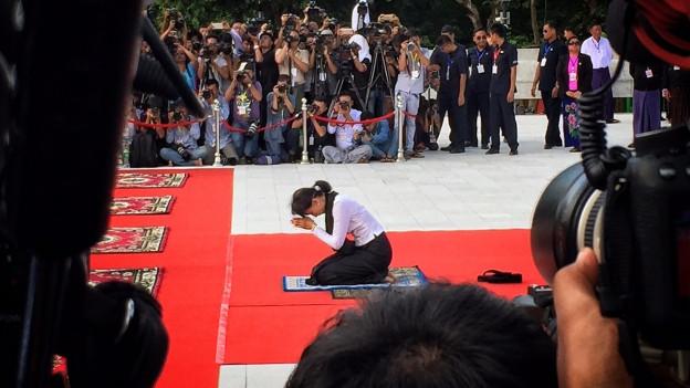 Suu Kyi auf rotem Teppich knieend, im Hinter- und Vordergrund Pressefotografen
