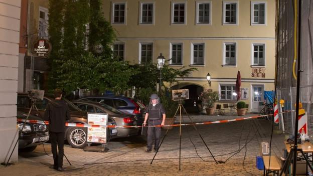 Nachtaufnahme von einem Gebäude in Ansbach, im Vordergrund ist die Polizei mit Aufräumarbeiten beschäftigt.