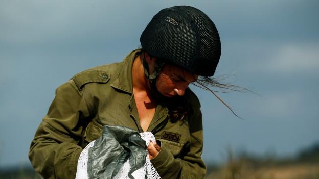 Israelische Soldatin in einem Tarnanzug und mit einem schwarzen Helm. Sie blickt zur Seite, so dass ihr Gesicht schlecht erkennbar ist.