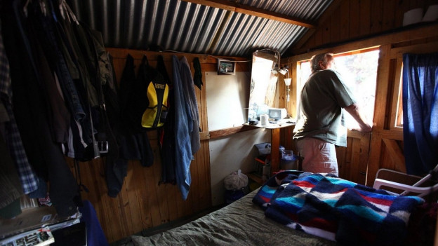 Ein Mann steht in einer ärmlichen Holzhütte in der Stube und sieht aus dem Fenster ins Freie.