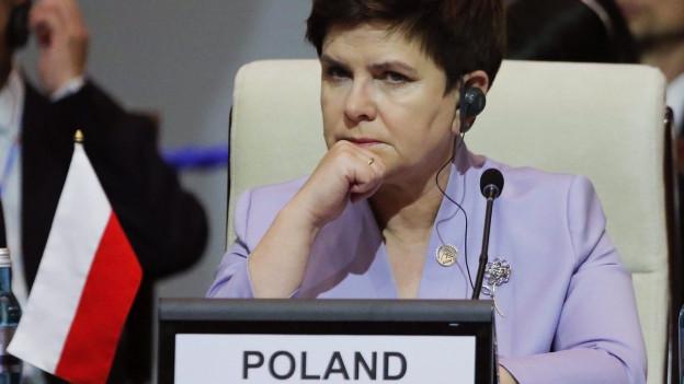 Beata Szydlo sitzt mit gerunzelter Stirn in einem Plenarsaal, sie trägt Kopfhörer.