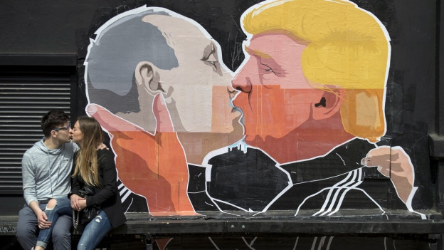 Bruderkuss: Ein Paar vor einem Plakat in der litauischen Hauptstadt Vilnius, auf dem Trump und Putin sich küssen.