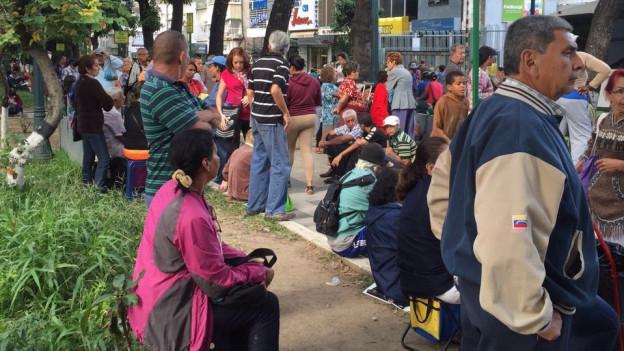 Stehende und sitzende Menschen am Strassenrand vor Ladengeschäften