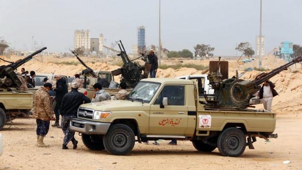 Soldaten der libyschen Einheitsregierung stehen vor Sirte, schwer bewaffnet und mit Pickups.