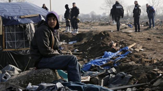 Ein Flüchtling sitzt vor einem zusammengeschusterten Zelt. Um ihn herum Müll. Im Hintergrund mehrere Polizisten.