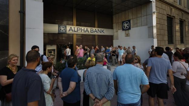 Eine lange Schlange steht vor dem Geldautomat einer griechischen Bank.