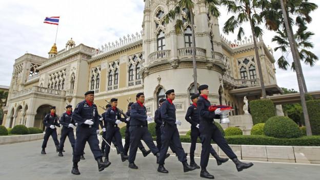 Thailändische Polizisten marschieren vor dem Sitz der Regierung und tragen die thailändische Nationalflagge für die tägliche Nationalhymne.
