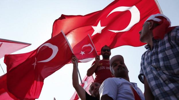 ¨Männer schwingen türkische Fahnen während einer Kundgebung in Istanbul.