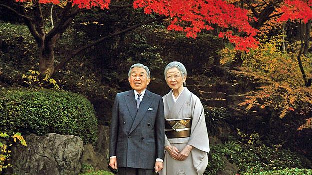 Kaiser Akihito und Kaiserin Michiko stehen unter einem Ahornbaum mir roten Blättern.