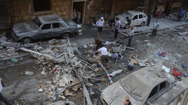 Luftaufnahme eines zerbombten Stadtteils von Aleppo, viele Trümmer und zerbombte Autos, Männer irren umher (11. Juli 2016).