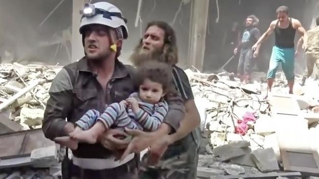 Ein Mann trägt ein verletztes Kind durch die Trümmer von Aleppo (28. April 2016).