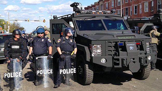 Polizisten in Kampfmontur stehen vor einem gepanzerten Einsatzfahrzeug in einer Strasse von Baltimore.