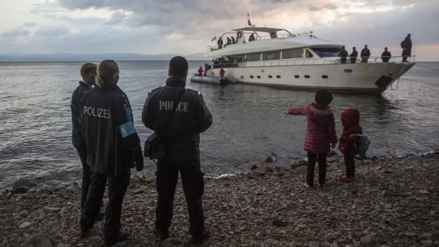 Mehrere Polizeibeamte bewachen eine Yacht an der Küste der griechischen Insel Lesbos.