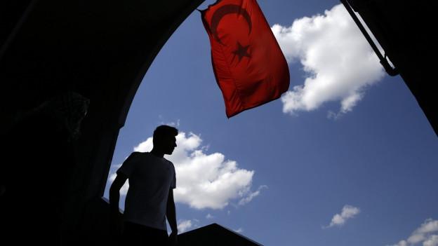 Ein Fußgänger läuft unter einer türkischen Flagge in Istanbul durch.