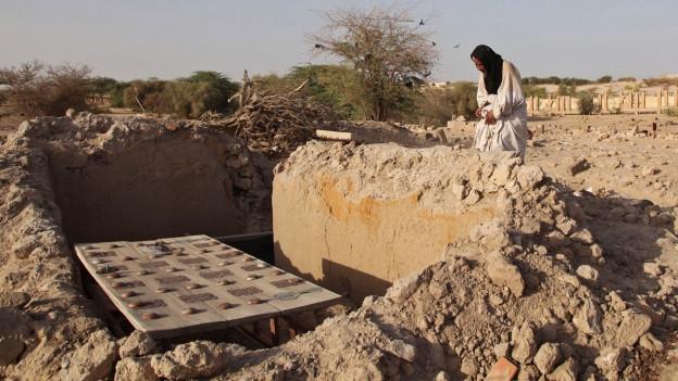 Ein Mann steht vor einem zerstörten Grab in Timbuktu, er schaut hinunter, ein Tuch um den Kopf geschlungen (4. April 2014).