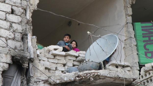 Zwei Kinder in Aleppo schauen durch ein grosses Loch in der Hauswand auf die Strasse hinunter (11. Februar 2016).