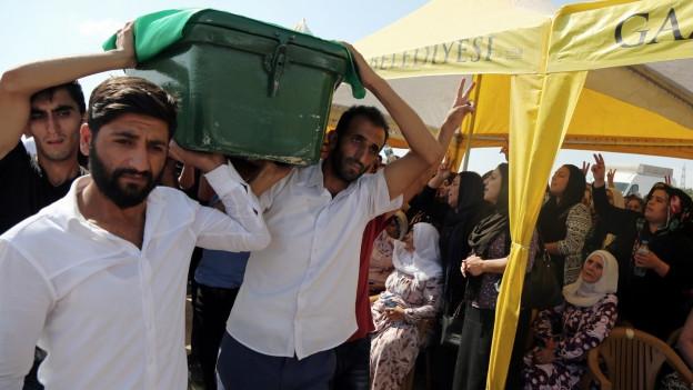 Männer in Gaziantep tragen den Sarg eines Anschlagsopfers zu Grabe, daneben klagen beklagen Frauen den Toten in einem Zelt..