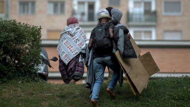 Menschen mit Gepäck von hinten fotografiert.