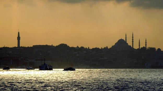 Die abendliche Skyline von Istanbul. Unter anderem zeichnet sich der Umriss einer Moschee ab. Im Vordergrund glitzert der Bosporus.
