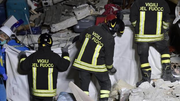 Drei Feuerwehrmänner, Tuch, Trümmer.